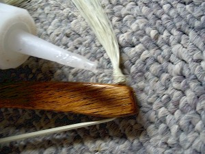Thin cyanoacrylate glue (super glue) is applied and allowed to wick deep into the knot's core