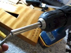 An old tuning wrench was modified into a tuning pin driver for use in a cordless drill