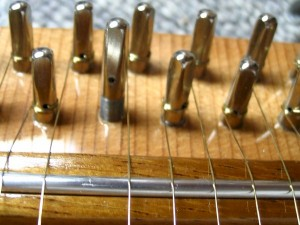 The tuning pin will begin higher than the rest, and will end up even as the string is wound on