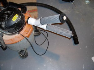 A set of activated carbon tubes are attached to the exhaust of a shop vacuum to filter the air