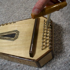 A special tuning wrench fits the tuning pins at the base of the psaltery